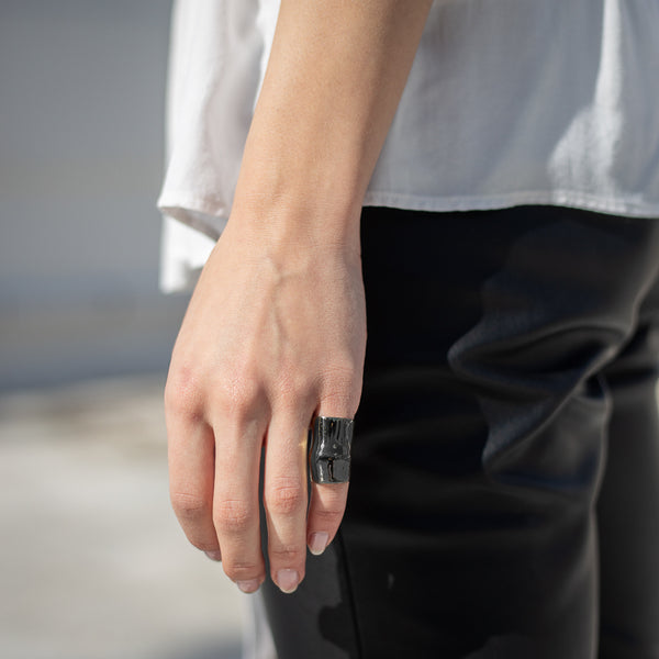 close up woman's hand, wearing black ring, punch