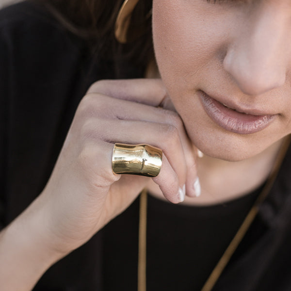 model in black, wearing punch ring, gold by 3rd-floor