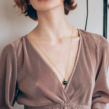 Load image into Gallery viewer, Cropped photo from collar bone to waist. Individual in a white polka dot shirt, wearing a gold, long chain necklace