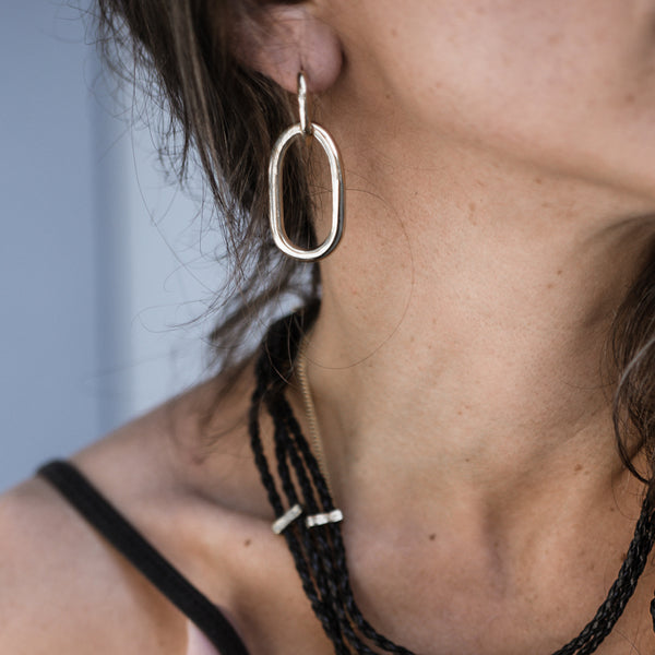 model with Massive, loop chain earrings, in silver plated brass
