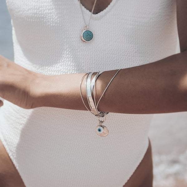 woman at the beach, wearing, Handmade Thallo bracelet, consisting of 7, uneven in size separate bracelets