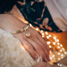 Load image into Gallery viewer, Close up of a female hand, rested on the arm of a couch. On her wrist she is wearing a handmade, gold, Turtle Luck bracelet