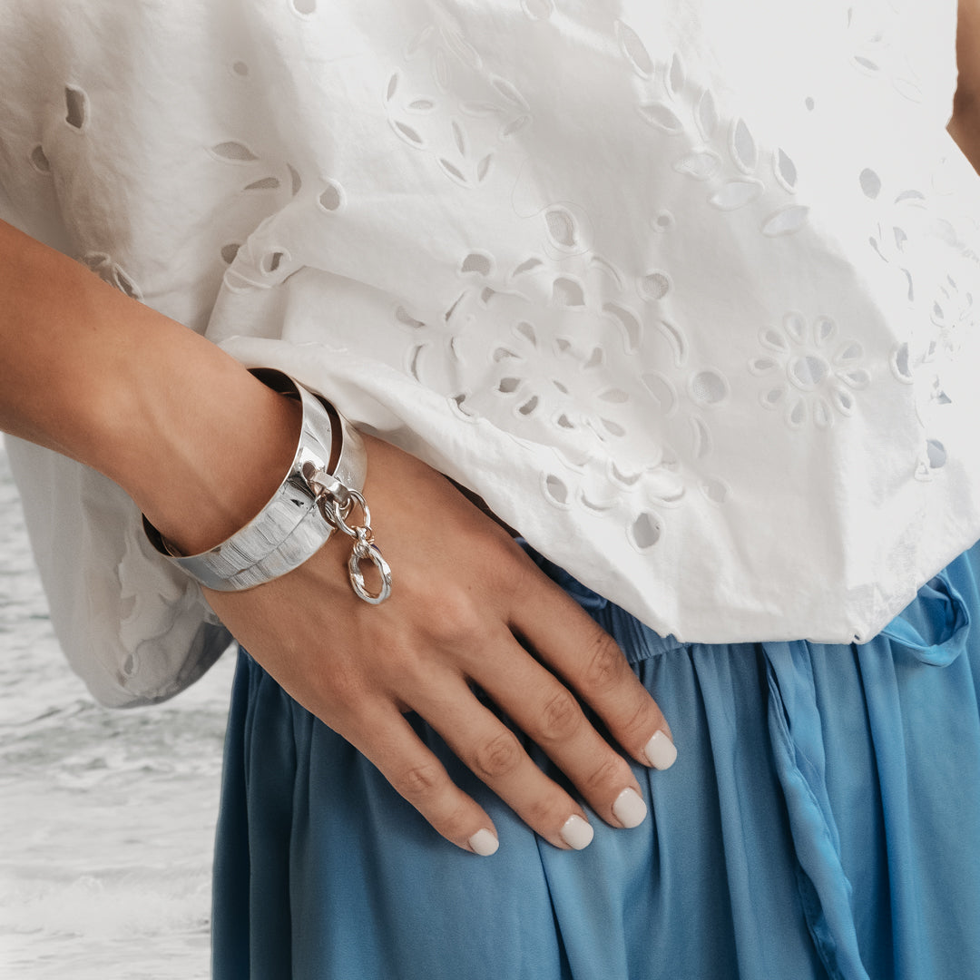 Woman in blue a trouser. On her left wrist, she is wearing a Vogue, double bangle, silver plated brass, handmade bracelet