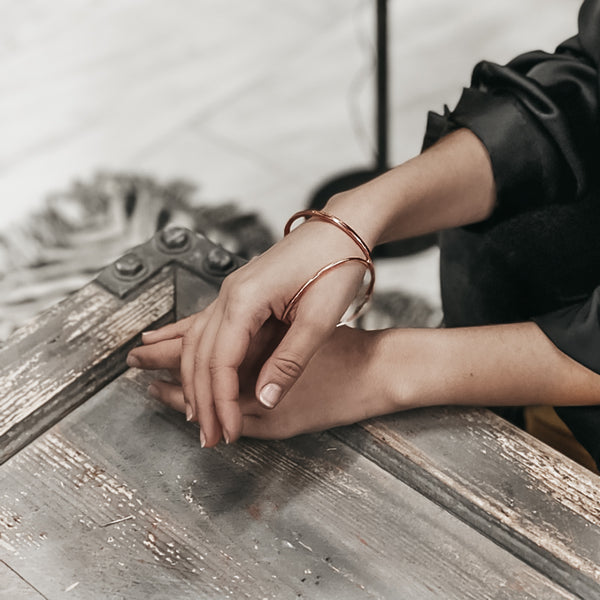 Photo of female's hands, on an etched, wooden surface. Her right hand, over her left. She is wearing a pink, statement bracelet by 3rd Floor