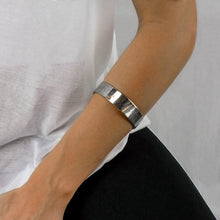 Load image into Gallery viewer, girl's forearm with a silver coordinates stamped bracelet by 3rd Floor handmade jewellery