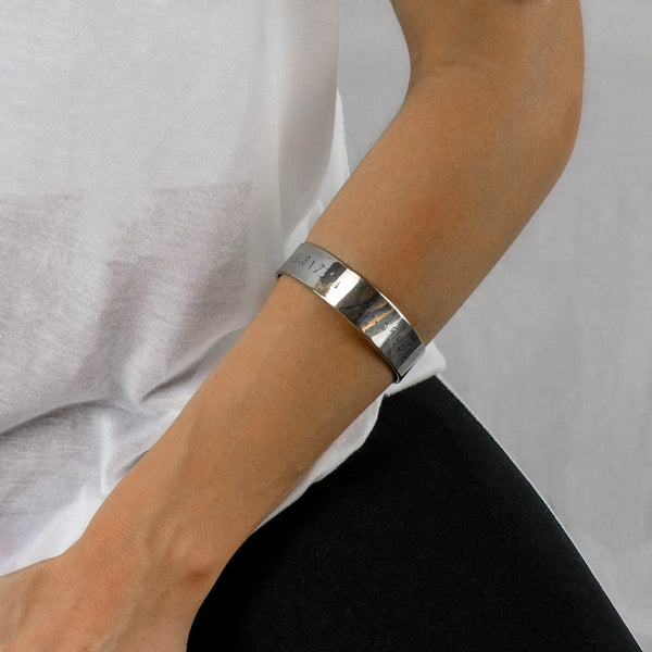 girl's forearm with a silver coordinates stamped bracelet by 3rd Floor handmade jewellery
