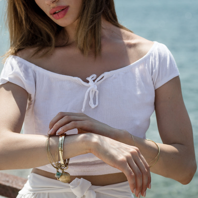 woman near the sea with Thallo Shell. Gold plated brass, handmade bracelet