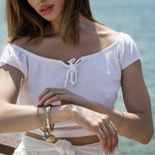 Load image into Gallery viewer, woman near the sea with Thallo Shell. Gold plated brass, handmade bracelet