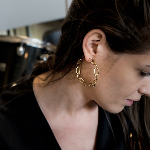 girl in profile wearing gold plated looped hoop earrings