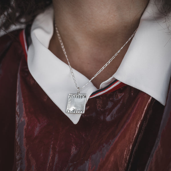 Female in burgundy blouse with white collar. On her neck she is wearing a silver plated silver, Equinox necklace