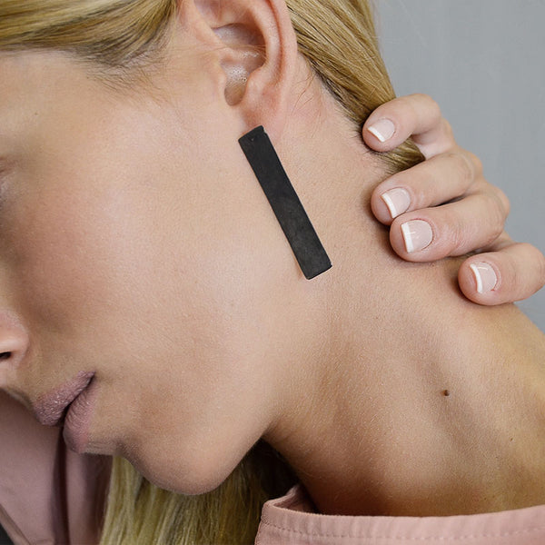 Close up of blond female's ear/neck. She is wearing a black, rectangular, pendant earring by 3rd Floor Handmade Jewellery