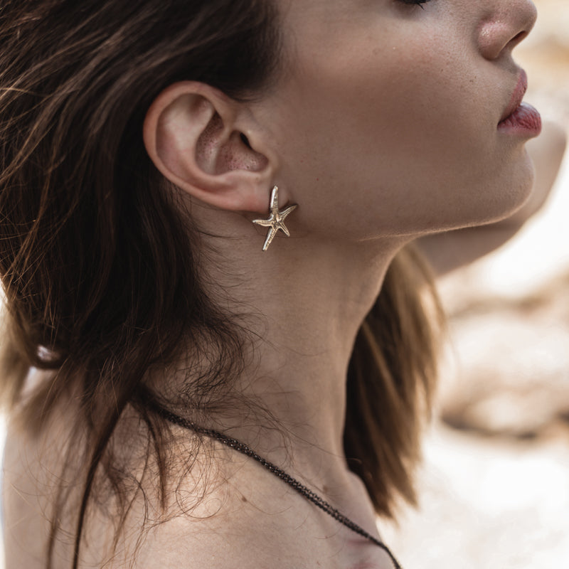 girl on the beach wearing Small Starfish, handmade earrings gold