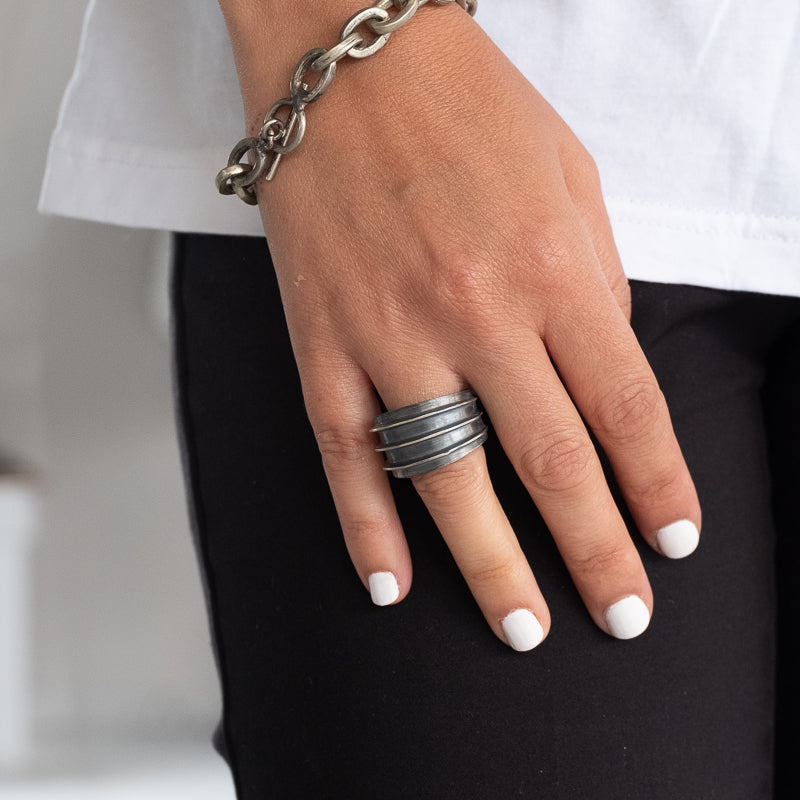 Woman's hand wearing Morton wide ruthenium plated silver plated ring with 3 peripheral debossed lines