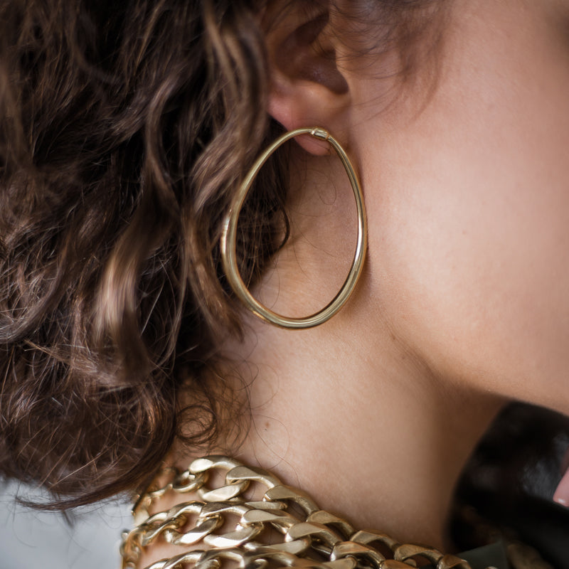 woman wearing gold earrings loop