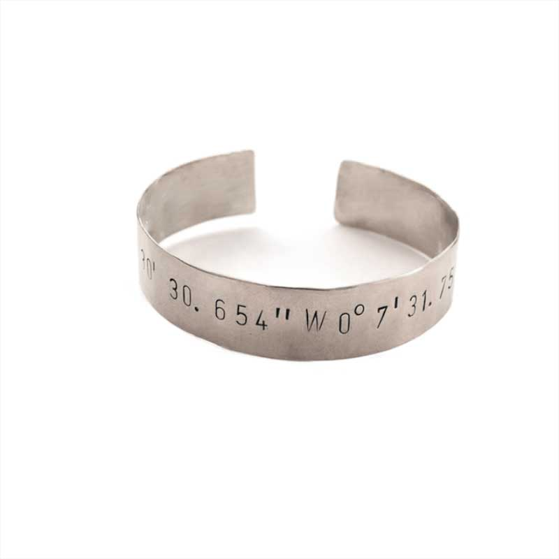 Wide adjustable silver plated cuff stamped with longitude and latidue coordinates