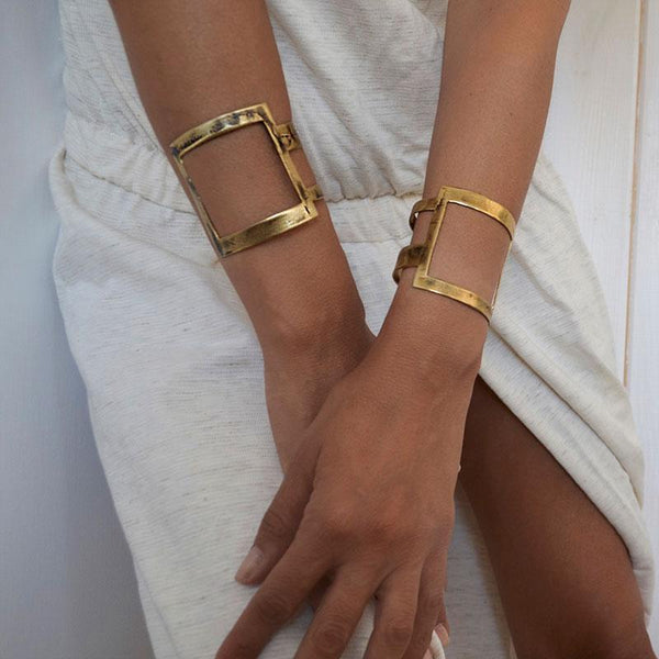 woman in white dress wearing,square bracelets, gold