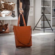 Load image into Gallery viewer, woman in black outfit holding Madeleine, Handmade, oblong leather bag, by 3rd Floor workshop