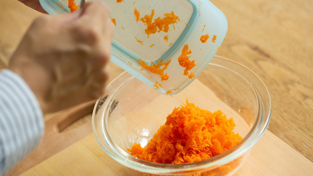 adding carrots to bowl for honey salad dressing
