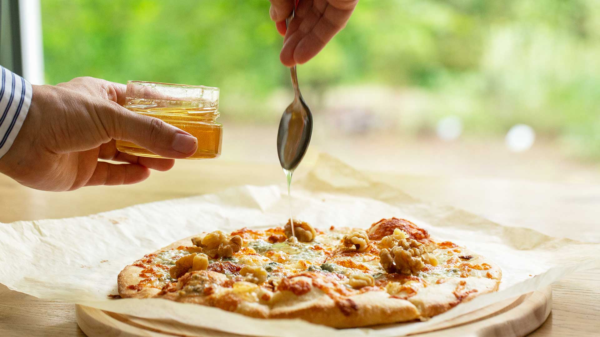 pouring raw honey on gorgonzola pizza
