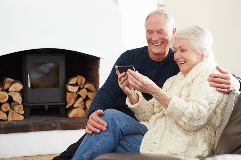 Elderly couple smiling at smartphone by a fireplace