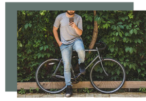 Man with a bike leaning against the wall checking his smart phone