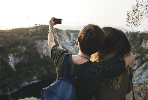 Two friends taking a picture in front of a mountain