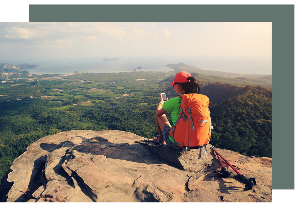 Backpacker on mountain with smartphone