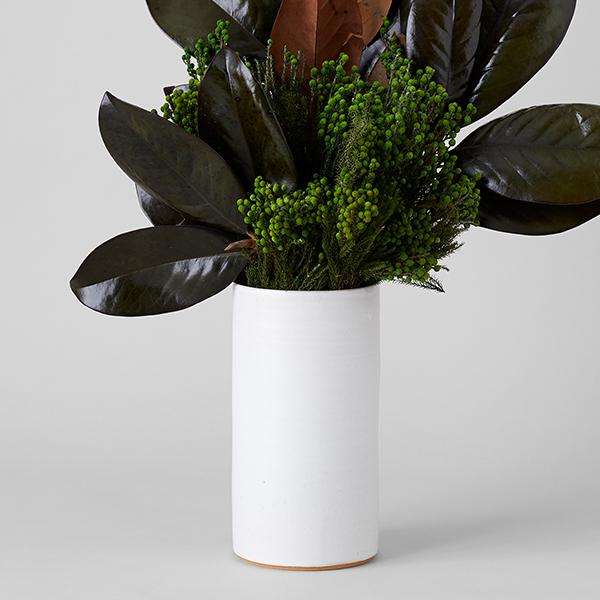 A white vase with beautiful dark motif leaves and florals