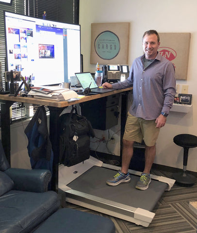 Jonathan Ferebee standing on his Unsit Treadmill Desk, short from back left