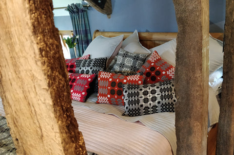 The image features a made bed, with Welsh Tweed Tapestry cushions scattered decoratively.