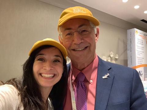 "Emily Sauer and Irwin Goldstein wearing matching ""Pain is Not a Weakness"" hats."