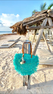 Azure raffia beach bag on sandy beach near cabana,
