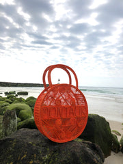 "Orange Crush 100 % Handwoven Black, Iraca Palm Bag with ""Montauk"" Woven Across Front On rocks near ocean"