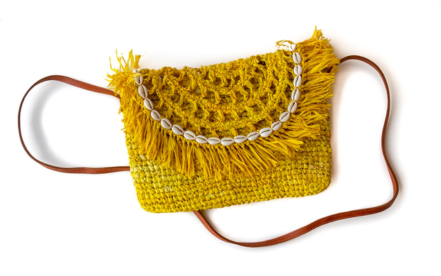 Primrose Yellow Handwoven Palm Clutch with Natural Shells with strap shown