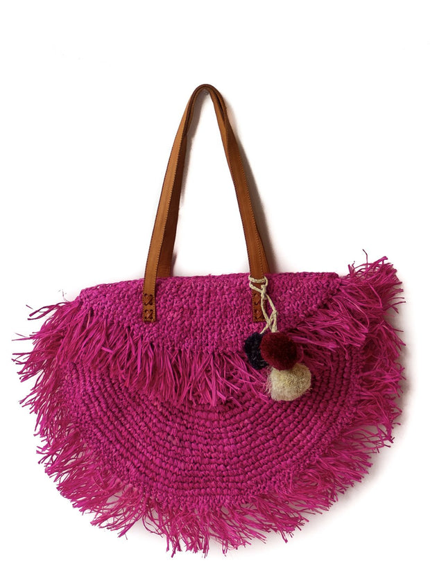 Hot pink raffia beach bag with leather strap.
