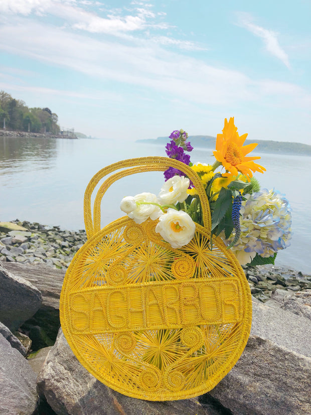 "Primrose Yellow 100 % Handwoven, Iraca Palm Bag with ""Sagharbor"" Woven Across Front on beach with flowers"