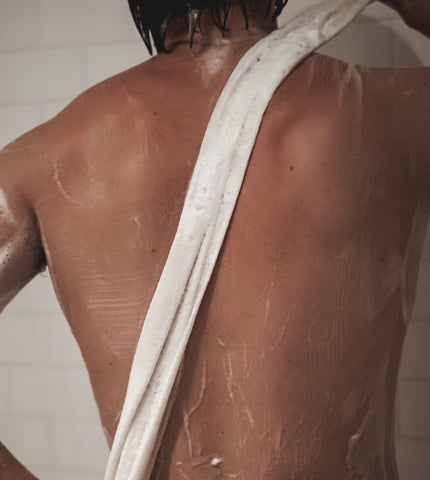 man's back with exfoliating towel in shower