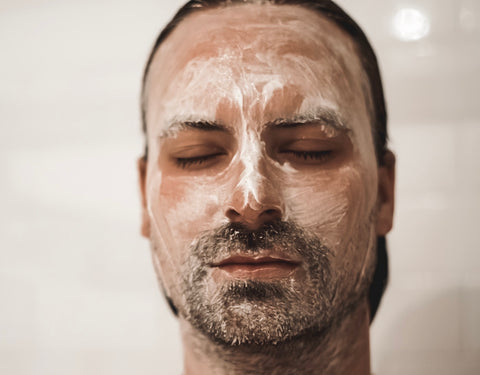 close up of man with exfoliating soap on his face, eyes closed