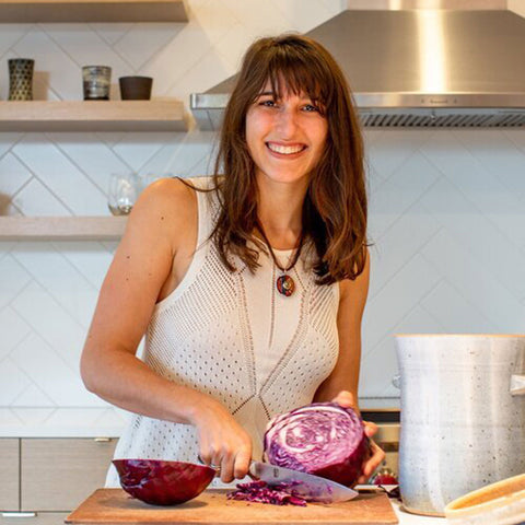 The author of JUNE's blog post Boy Mamas stands in her kitchen chopping up lettuce.