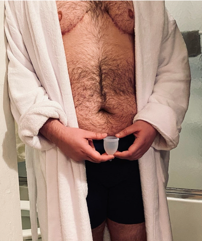 Transman holding a menstrual cup while wearing a robe