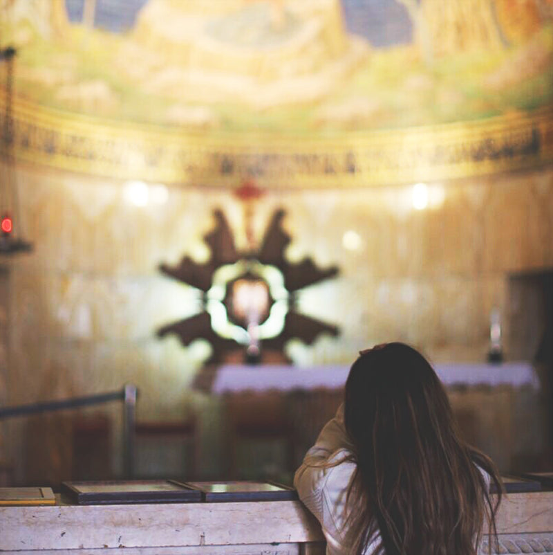 young girl kneeling at an altar railing glowing altar paintings