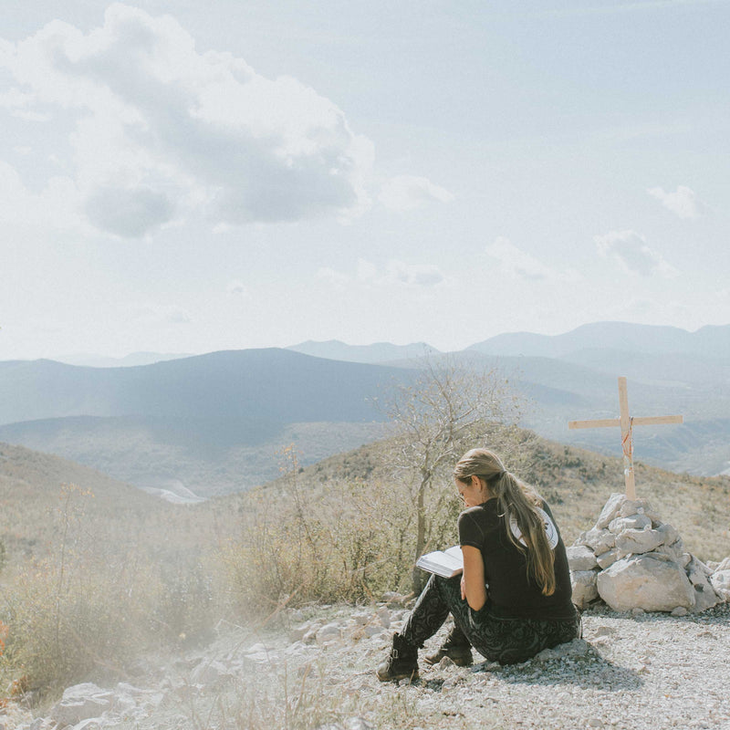 Woman seated on ground next to wooden cross reading, overlooking canyons.
