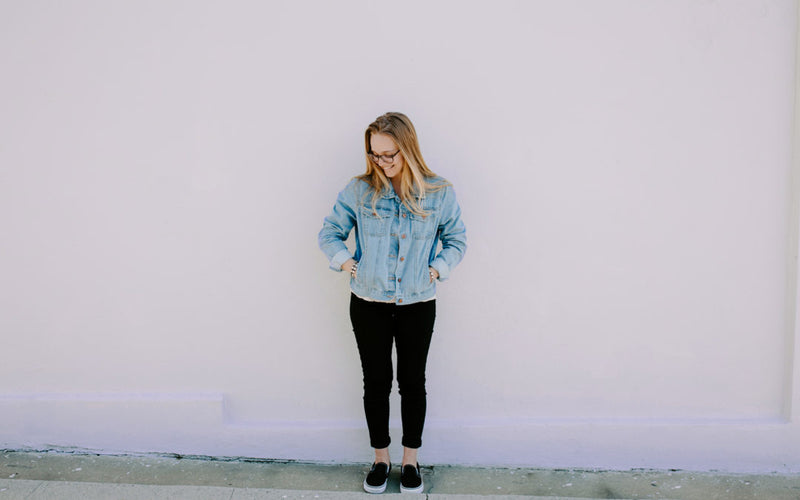 young woman wearing Divine Mercy Blessing bracelets, denim jacket and black pants standing against a plain outdoor wall hands in pockets