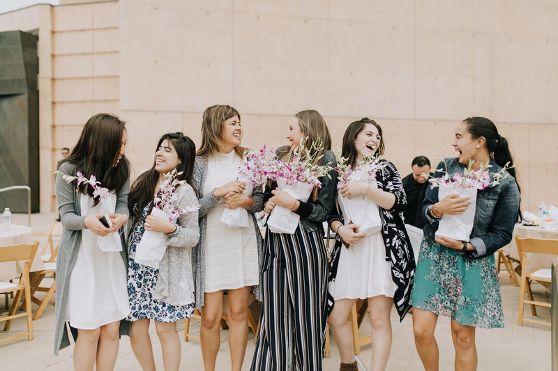 group of young women holding white paper bags of orchid flowers, laughing and chatting together