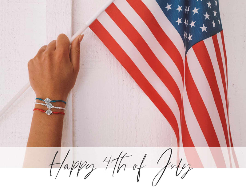Hand wearing Red White Blue Blessing Bracelets Holding an American Flag