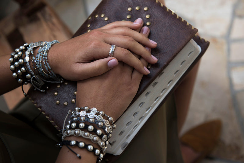 young woman's hands folded on bible, wearing Hail Mary Morse Code bracelet and other My Saint My Hero Blessing Bracelets