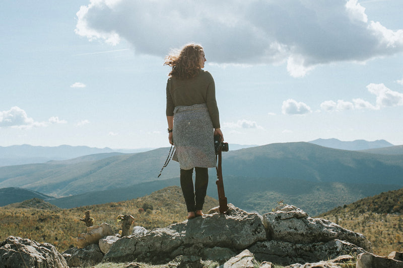woman standing on a rise overlooking hills