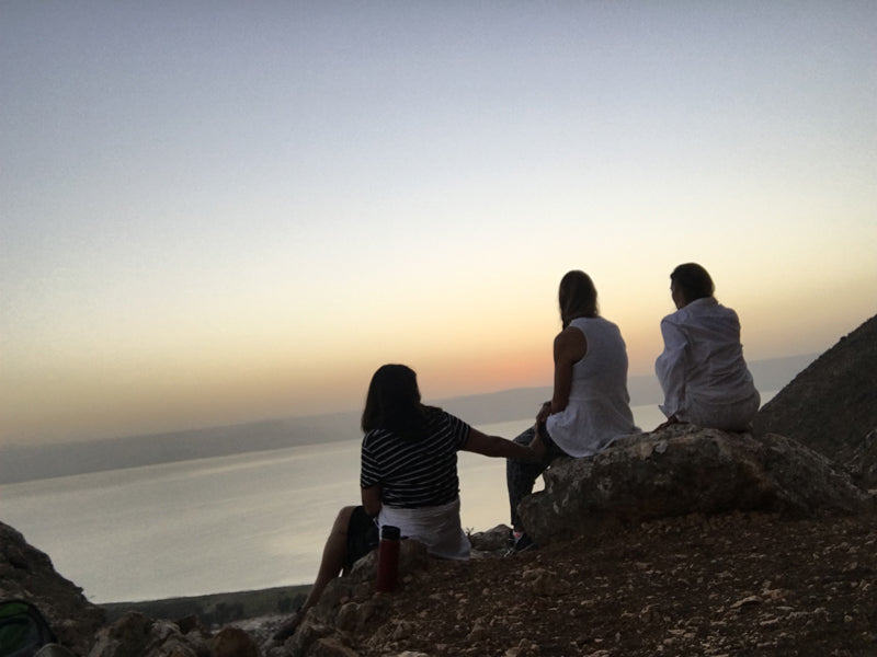 Three women seated on cliff overlooking the sea at sunset