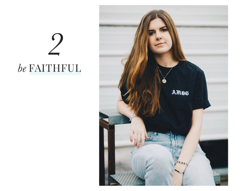 Maclaine seated wearing black t-shirt - text: Be Faithful