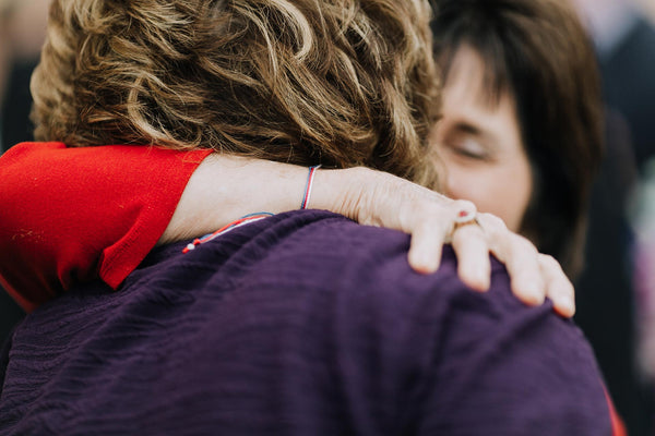 United in prayer and blessing. Two women hugging.